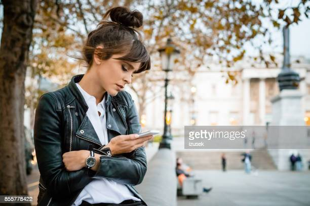 worried woman using smart phone at trafalgar square in london, autumn season - a fall from grace stock pictures, royalty-free photos & images