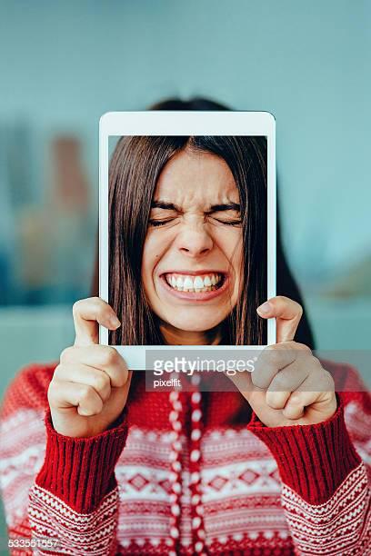 Worried woman with digital tablet making selfie