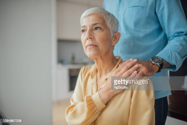 worried woman with male hand on her shoulder - hand on shoulder stock pictures, royalty-free photos & images