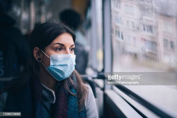 worried woman with protective face mask in bus transport. - corona virus stock pictures, royalty-free photos & images