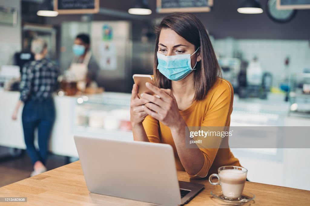 Worried woman with protective mask, cell phone and laptop : Stock Photo
