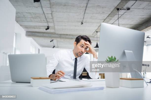 worried young businessman working in office - izusek stock pictures, royalty-free photos & images
