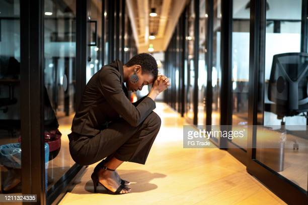 worried young businesswoman at corridor office - downsizing unemployment stock pictures, royalty-free photos & images