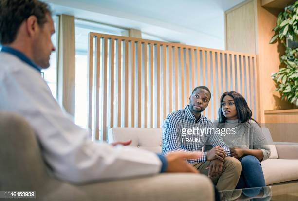 Worried young couple listening to doctor in a hospital.