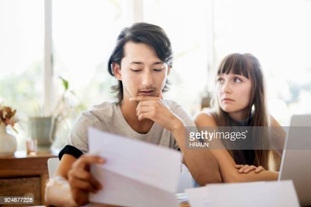 心配している若いカップル読み取り文書自宅 - ガールフレンド ストックフォトと画像