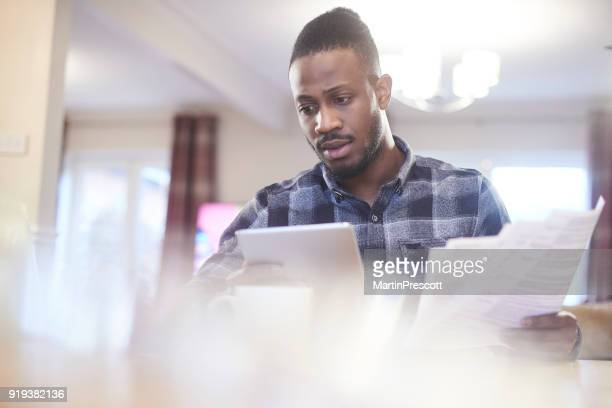 Worried young male reading through household bills and checking bank statement online