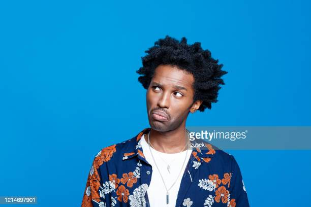 worried young man in hawaiian shirt against blue background - worried stock pictures, royalty-free photos & images