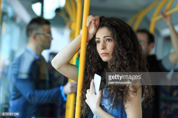 worried young woman traveling inside of a bus - harassment stock photos and pictures