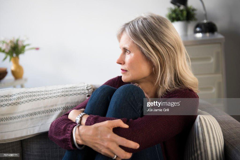 Worrying Caucasian woman hugging legs : Stock Photo