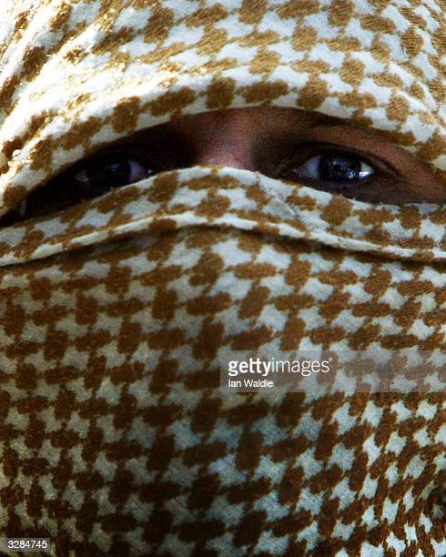 A worshiper at Finsbury Park Mosque disguises his face as members of the extreme rightwing group the National Front hold a demonstration during...