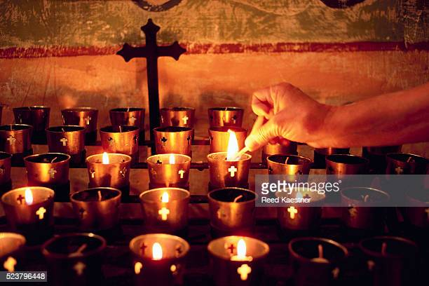 worshiper lighting votive candle on altar - cero foto e immagini stock