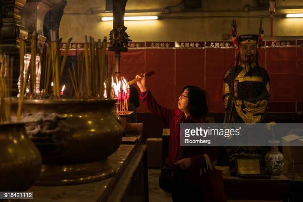 A worshiper lights incense the at Man Mo Temple in Hong Kong China on Wednesday Feb 14 2018 The city's financial markets will close on Feb 16 for the...