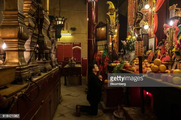A worshiper prays and offers incense at the Man Mo Temple in Hong Kong China on Wednesday Feb 14 2018 The city's financial markets will close on Feb...