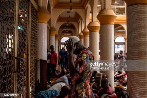 TOPSHOT A worshiper prays at the Central Mosque in Lagos during a special Jumu'ah prayer service on February 15 on the eve of Nigeria's presidential...