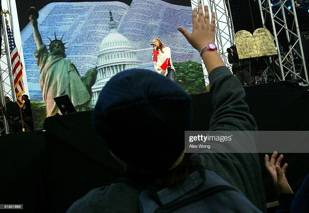 A worshiper raises her hand as she worships during the 'America for Jesus' rally October 22, 2004 at the National Mall in Washington, DC. Although the U.S. Constitution prohibits an official state religion, references to God appear on American money, the U.S. Congress starts its daily session with a prayer, and the same U.S. Supreme Court that has consistently struck down organized prayer in public schools as unconstitutional opens its public sessions by asking for the blessings of God. The Supreme Court will soon use cases from Kentucky and Texas to consider the constitutionality of the Ten Commandments displays on government property, addressing a church-state issue that has ignited controversy around the country.