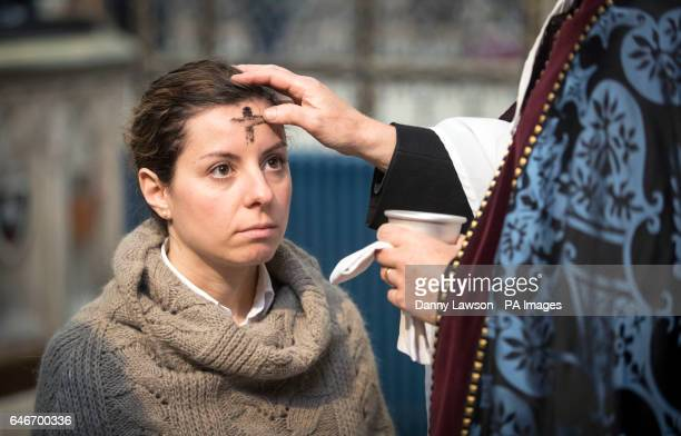 A worshiper receives the sign of the cross marked in ash on her forehead from the Reverend Canon Dr Christopher Collingwood during the Imposition of...