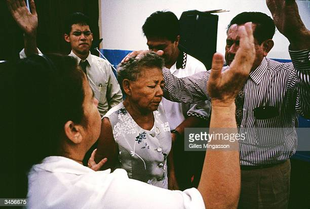 Worshipers asked for Jesus' help as they try to heal a women suffering from stomach pain at a storefront Pentecostal church March 15 2003 in...