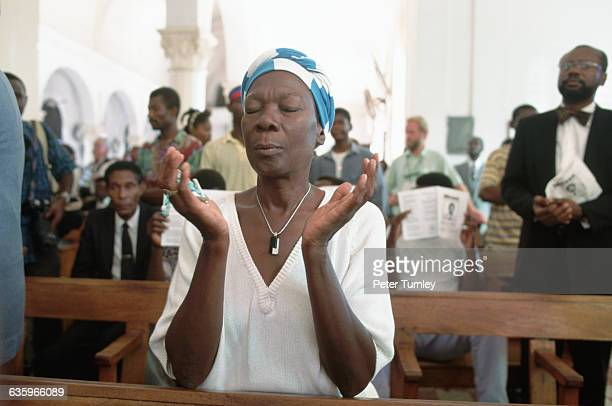 Worshipers attend a service celebrating the return of exiled Haitian president Jean Bertrand Aristide