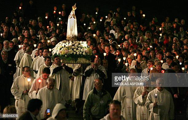 Worshipers, priests and staff of Fatima make a tour of the sanctuary following a lighted cross and a replica of the Virgin Mary of Fatima, infront...