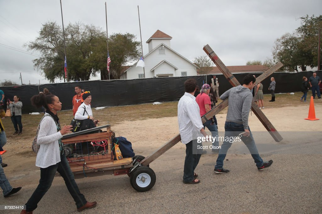 Worshipers pull a cross past the church following Sunday service at the temporary First Baptist Church of Sutherland Springs on November 12, 2017 in Sutherland Springs, Texas. The service was held in a tent on the site of the town's baseball field. Residents of the community are still trying to heal following the shooting at the original church building on November 5. Devin Patrick Kelley shot and killed the 26 people and wounded 20 others when he opened fire during Sunday service at the church.