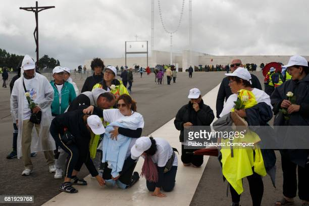A worshipper carries a baby as she walks on her knees in the Sanctuary of Fatima on May 11 2017 in Fatima Portugal Pope Francis will be attending the...