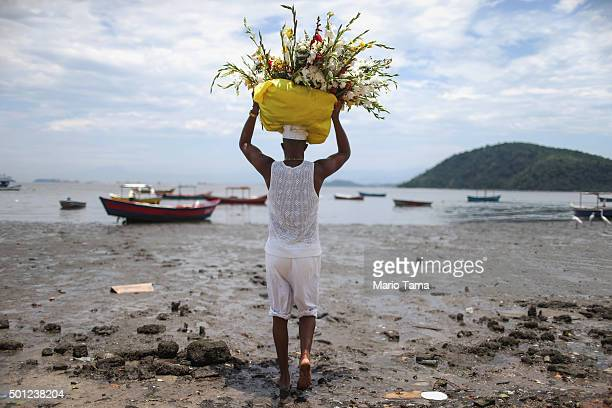 A worshipper carries flowers to be left in the water as offerings on Guanabara Bay during a Candomble ceremony honoring goddesses Iemanja and Oxum on...