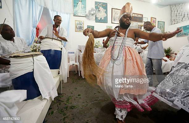 A worshipper dances dressed as the goddess Iansa after falling into a trance during a Candomble ceremony on August 17 2014 in Cachoeira Brazil...