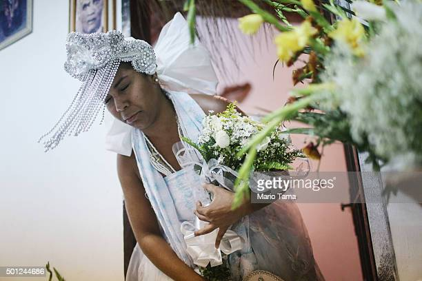 A worshipper dressed as Oxum bows during a Candomble ceremony honoring goddesses Iemanja and Oxum on December 13 2015 in Itaborai Brazil Candomble is...