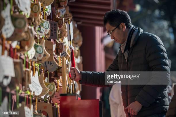 A worshipper holds a 'Hamaya' arrow as he prays for the new year at Tsurugaoka Hachimangu Shinto shrine on January 1 2018 in Kamakura Japan...