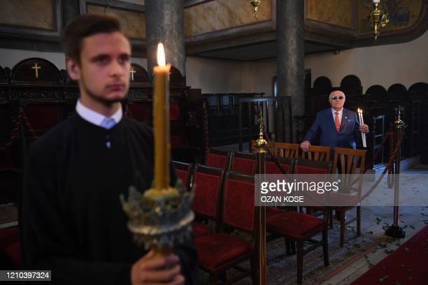A worshipper holds candles prior the arrival of the Ecumenical patriarch Bartholomew I spiritual leader of Greek Orthodox world for the Easter...