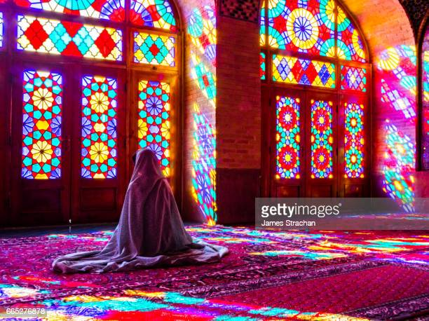 worshipper in front of stained glass windows of prayer hall, nasir-al molk mosque, shiraz, iran - muslim praying stock pictures, royalty-free photos & images