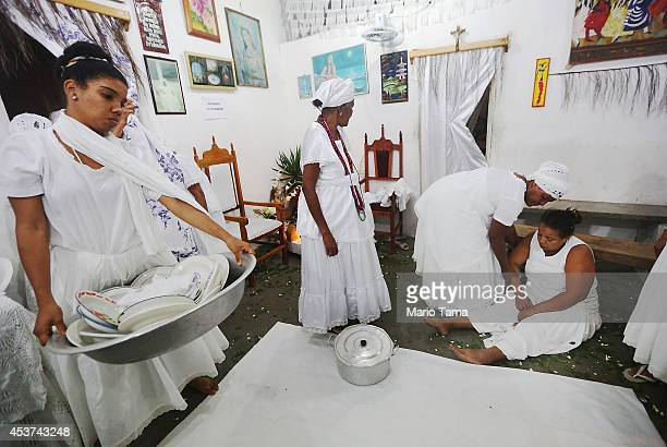 A worshipper is assisted after falling into a trance during a Candomble ceremony on August 17 2014 in Cachoeira Brazil Candomble is an AfroBrazilian...