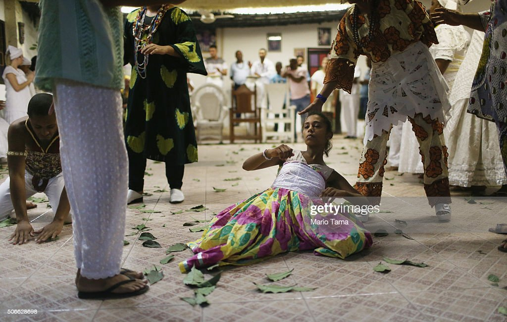 A worshipper (C) is overcome during a Candomble ceremony on January 24, 2016 in Itaborai, Brazil. Candomble is an Afro-Brazilian religion whose practitioners sometimes fall into trances during ceremonies believing they have become possessed by gods, or orixas. The roots of the Candomble religion came to Brazil via African slaves and eventually incorporated some elements of Catholicism. Some believers have faced persecution in Brazil and ceremonies are often conducted privately.