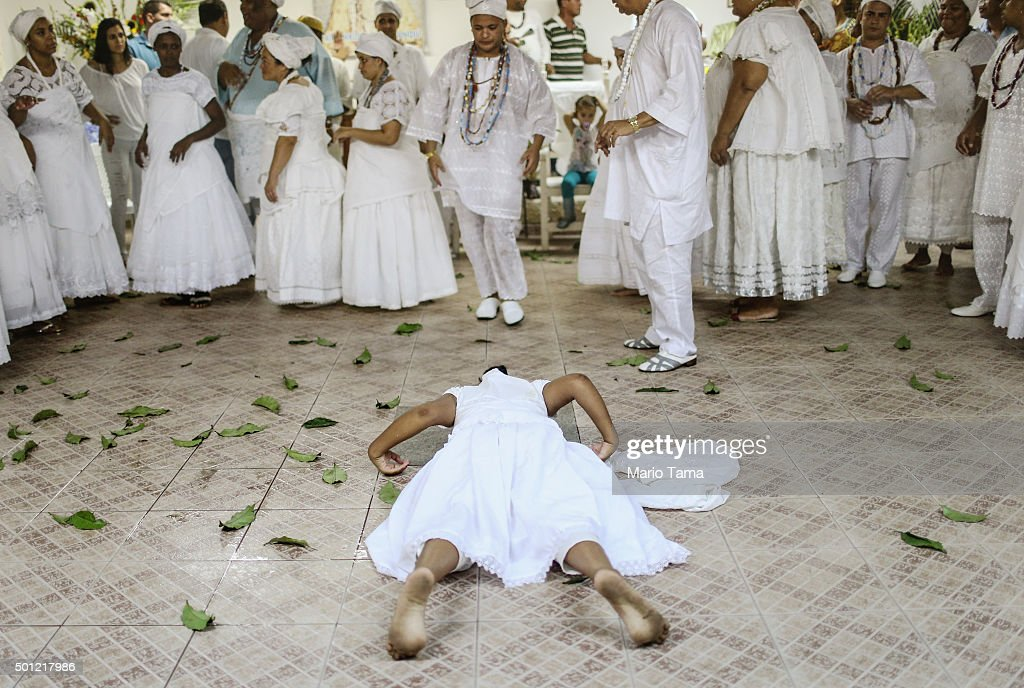 A worshipper lies on the floor during a Candomble ceremony honoring goddesses Iemanja and Oxum on December 12, 2015 in Itaborai, Brazil. Candomble is an Afro-Brazilian religion whose practitioners sometimes fall into trances during ceremonies believing they have become possessed by gods, or orixas. The roots of the Candomble religion came to Brazil via African slaves and eventually incorporated some elements of Catholicism. Afro-Brazilian religions generally refer to Iemanja as goddess of the sea and Oxum as goddess of rivers, lakes and waterfalls, or fresh water. Candomble practitioners sometimes face persecution in Brazil from other religious groups including evangelical Christians.
