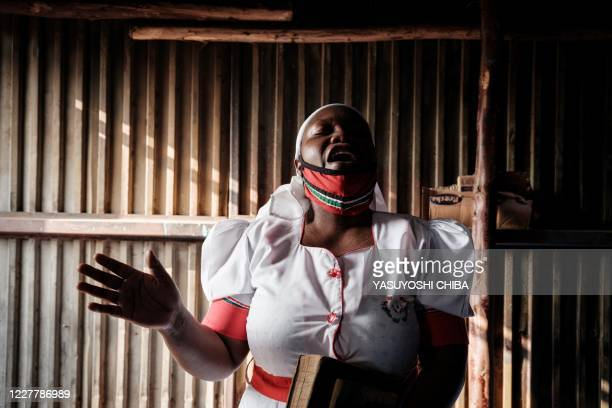 TOPSHOT A worshipper of the African Divine Church attends a prayer at their church in the Kibera slum of Nairobi on July 26 after Kenya's President...