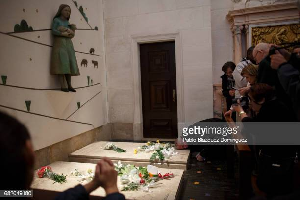 A worshipper prays in front of an image depicting shepherd Jacinta Marto at the Basilica of Our Lady of the Rosary in the Sanctuary of Fatima on May...