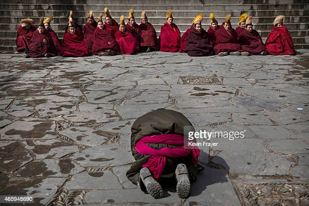 A worshipper prays in front of Tibetan Buddhist monks during Monlam or the Great Prayer rituals on March 5 2015 at the Labrang Monastery Xiahe County...