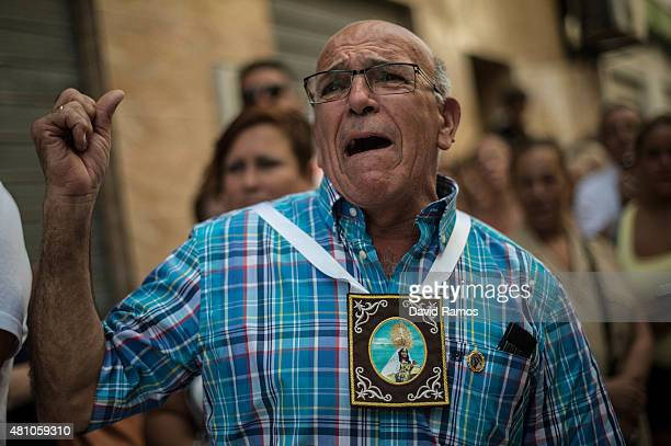 A worshipper reacts as penitents of the Brotherhood 'Virgen del Carmen de la Carihuela' carry the statue of Virgen del Carmen on their way to the sea...