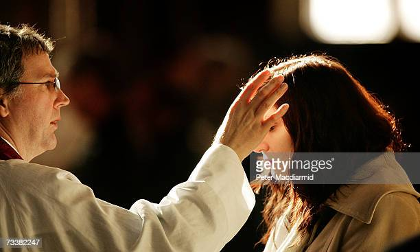 A worshipper receives a cross of ashes painted on her forehead from a priest during Ash Wednesday Mass at Westminster Cathedral on February 21 2007...