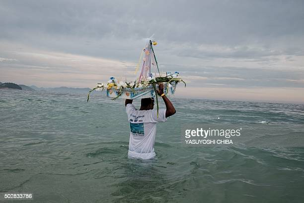 TOPSHOT A worshipper sends a handmade boat into the sea as a year end offering to Iemanja the Goddess of the Sea of the AfroBrazilian religion...