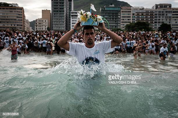 Worshipper sends a handmade boat into the sea as a year end offering to Iemanja, the Goddess of the Sea of the Afro-Brazilian religion Umbanda, at...