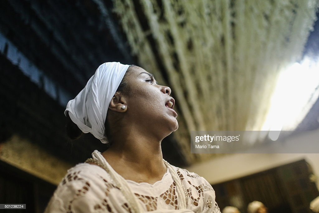 A worshipper sings during a Candomble ceremony honoring goddesses Iemanja and Oxum on December 12, 2015 in Itaborai, Brazil. Candomble is an Afro-Brazilian religion whose practitioners sometimes fall into trances during ceremonies believing they have become possessed by gods, or orixas. Male worshippers are sometime possessed by female deities. The roots of the Candomble religion came to Brazil via African slaves and eventually incorporated some elements of Catholicism. Afro-Brazilian religions generally refer to Iemanja as goddess of the sea and Oxum as goddess of rivers, lakes and waterfalls, or fresh water.