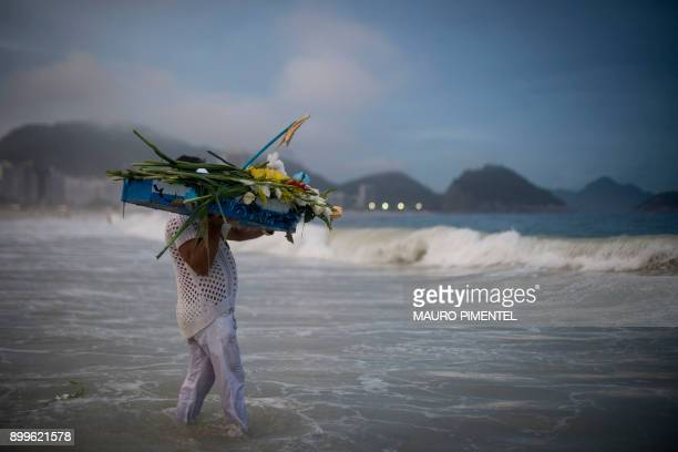 TOPSHOT A worshipper takes a handmade boat into the sea as endofyear offerings to Iemanja the Goddess of the Sea of the AfroBrazilian religion...