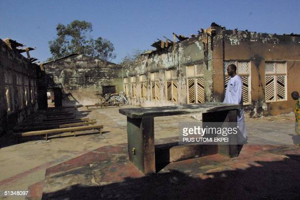 A worshipper walks 30 November 2002 among the debris of the Holy Cross Church in the northern Nigerian city of Kaduna Father James Odion Iyere a...