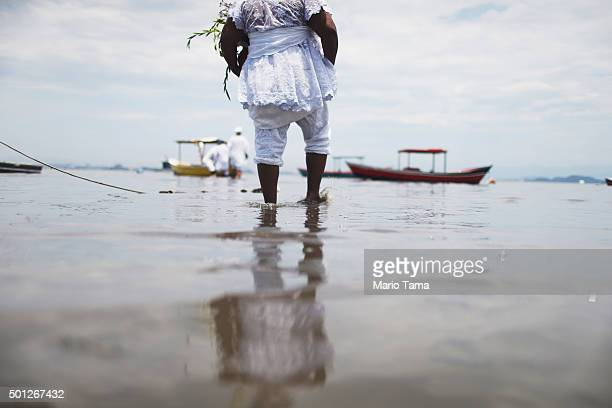 Worshipper walks with offerings to a boat on the edge of polluted Guanabara Bay during a Candomble ceremony honoring goddesses Iemanja and Oxum on...
