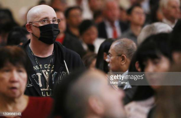 A worshipper wears a face mask to protect against the coronavirus while sitting in a pew at the Cathedral of Our Lady of the Angels on Ash Wednesday...