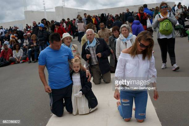 Worshippers and a girl walk on their knees at the Sanctuary of Fatima on May 12 2017 in Fatima Portugal Pope Francis will be attending the Sanctuary...