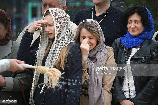 Worshippers are blessed with holy water outside Holy Transfiguration Cathedral on April 20, 2014 in Donetsk, Ukraine. The Easter baskets...