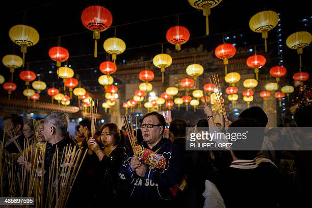 Worshippers burn incense and pray at the Wong Tai Sin Temple to welcome the Chinese New Year of the horse in Hong Kong on January 30 2014 Tens of...