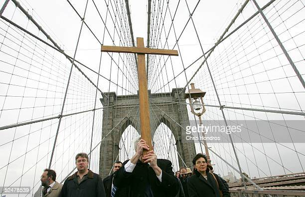 Worshippers carry a wooden cross across the Brooklyn Bridge on the Christian holiday of Good Friday March 25 2005 in New York City The procession...